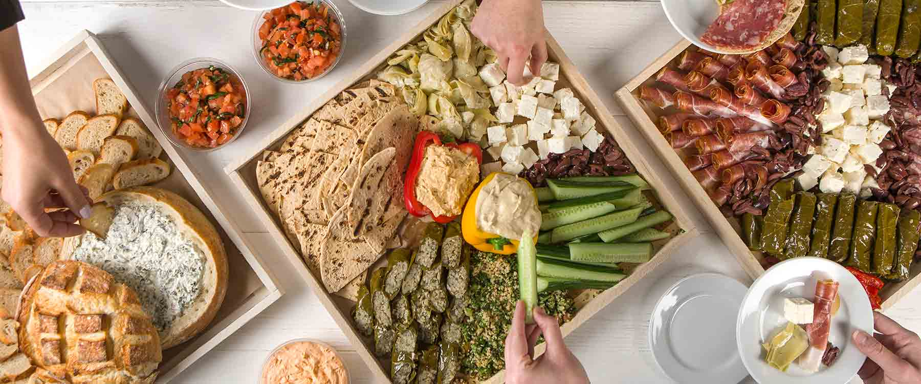 Hands filling plates from party platers