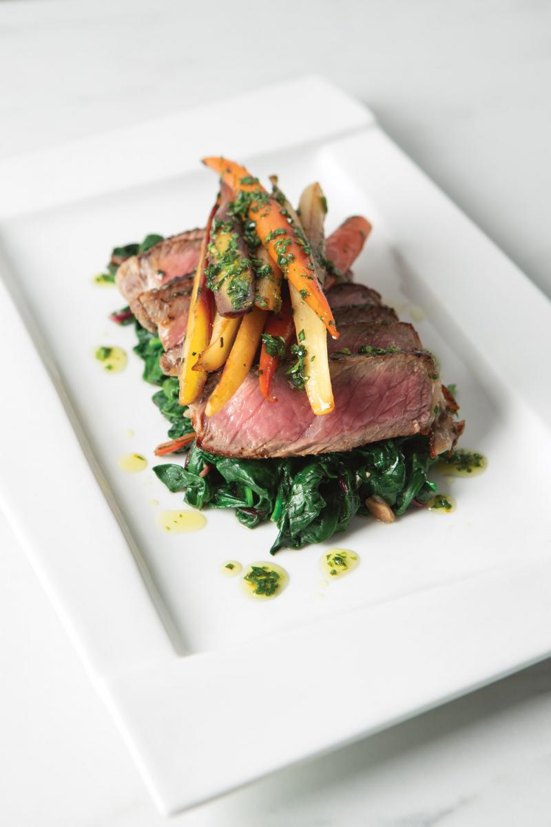 bison steak on plate with carrots and greens