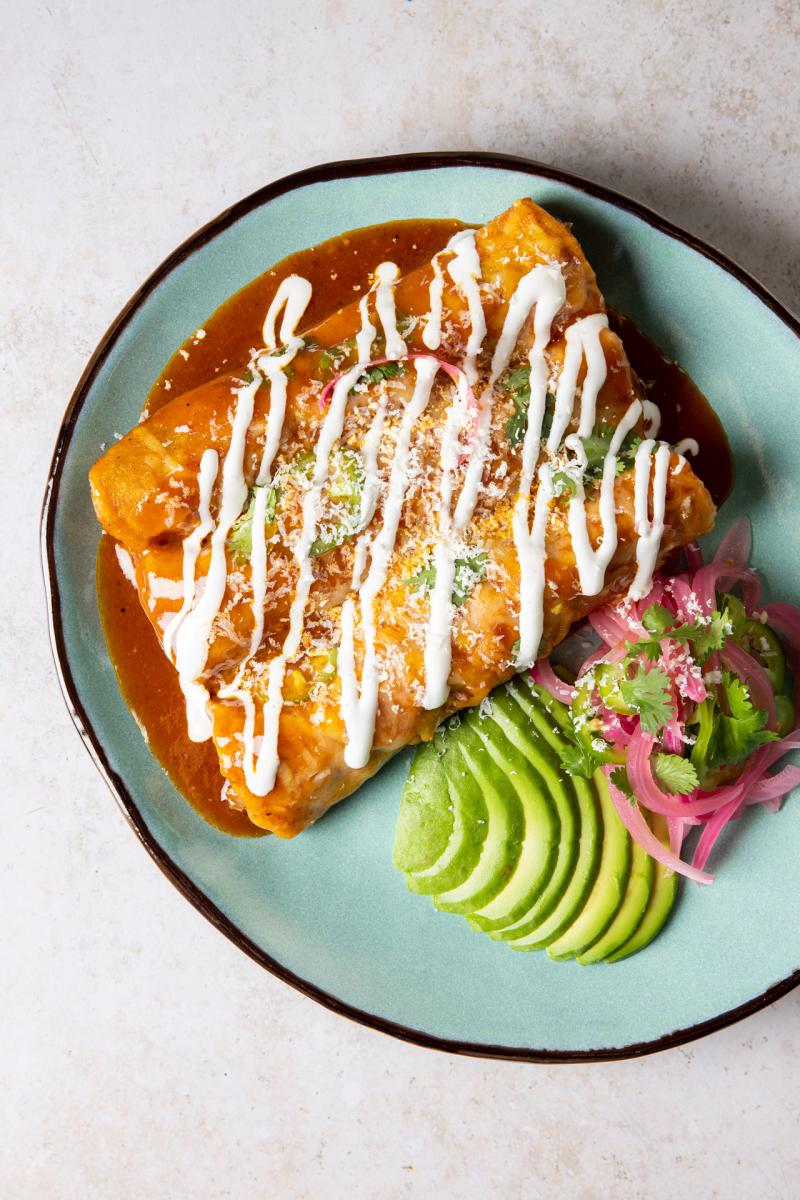 Top-down angle of three enchiladas on a plate with sliced avocado and pickled onions