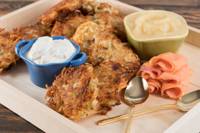 Potato Latkes on a tray with accompaniments