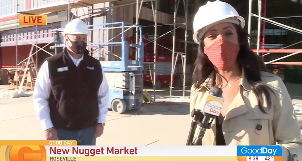 reporter and store director standing outside new Nugget Markets under construction
