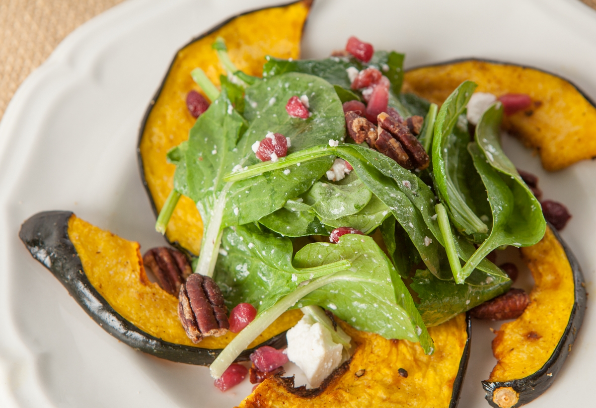 roasted acorn squash with greens and pomegranates