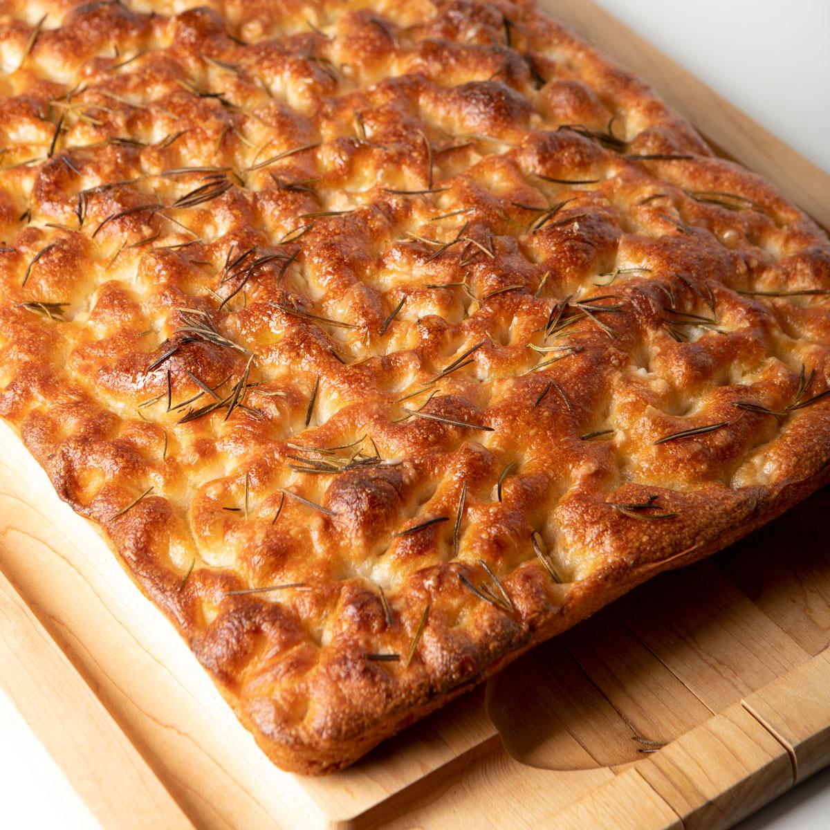 focaccia bread on a wooden cutting board
