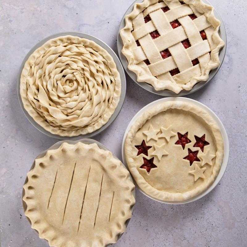 four uncooked pies with different crust decorations