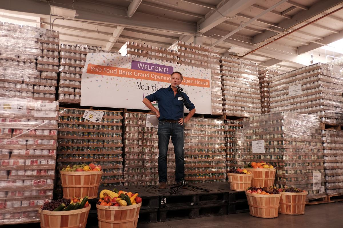 man on stage at yolo food bank warehouse