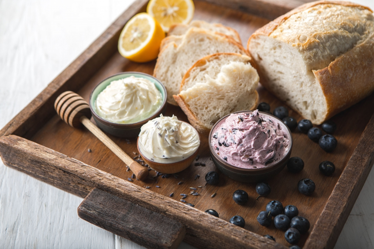 Three flavors of whipped butter with bread, lemons, honey and blueberries