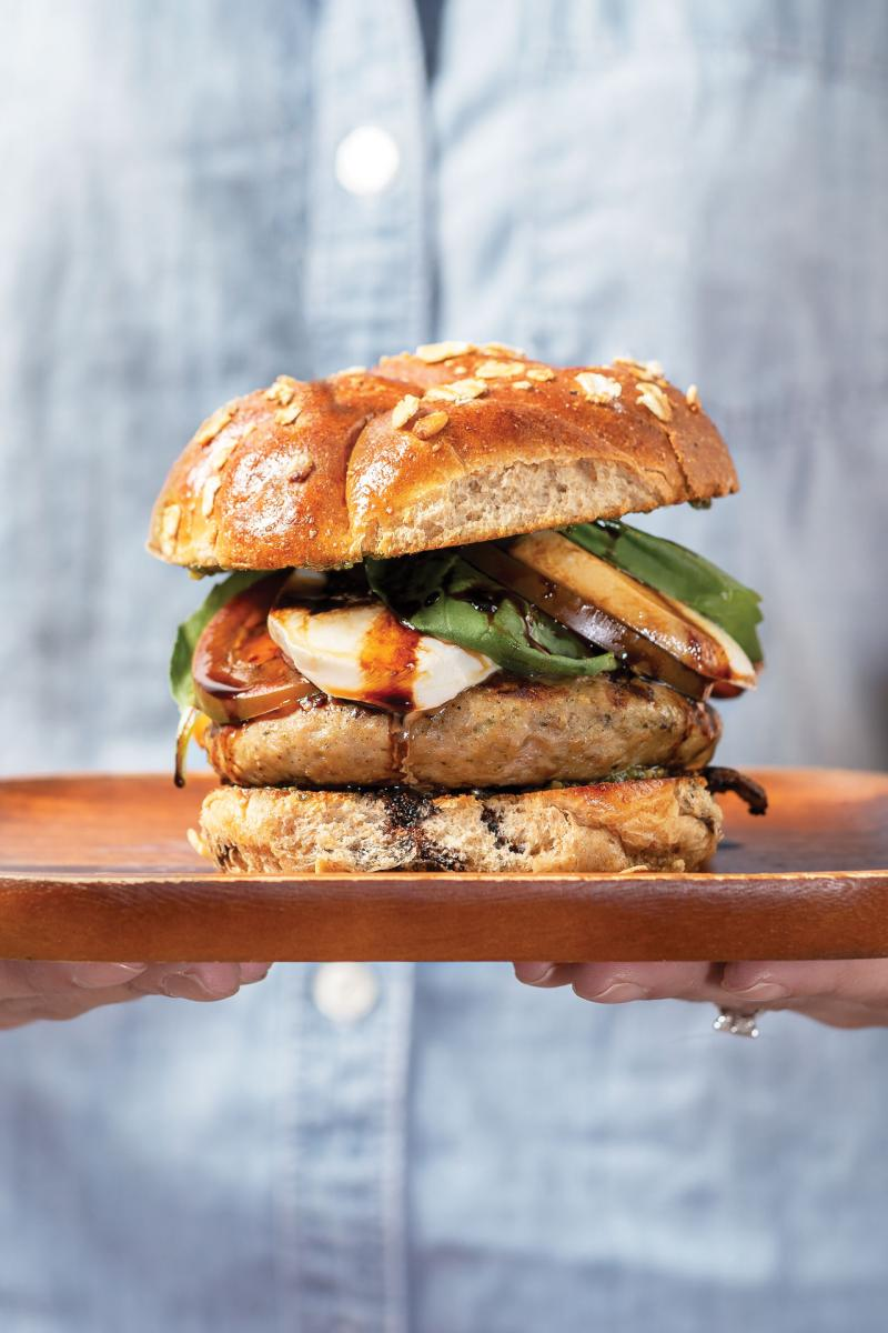 turkey caprese burger on a wooden plate held in someone's hands