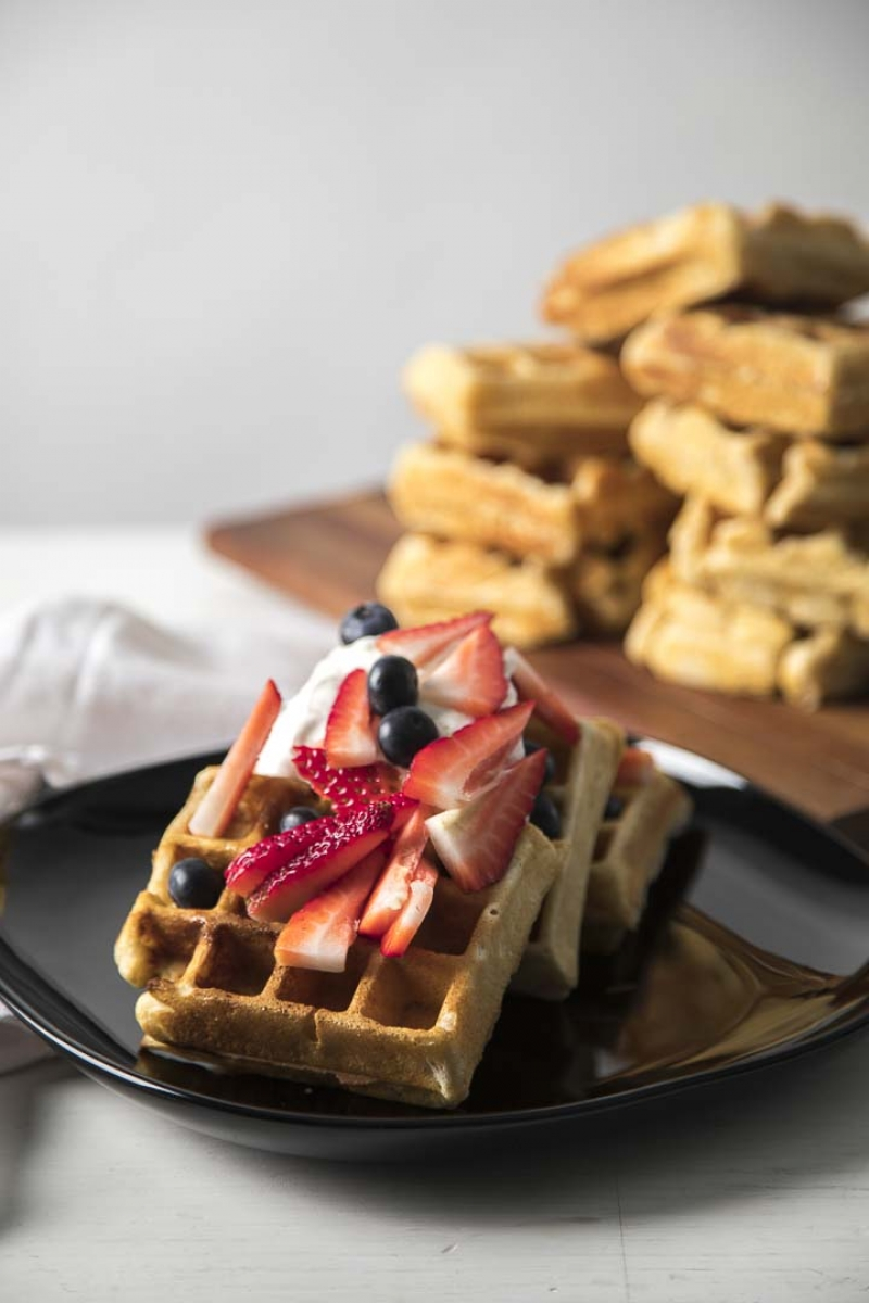 waffles and berries on a plate with whipped cream