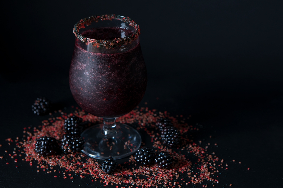 black cocktail surrounded by blackberries