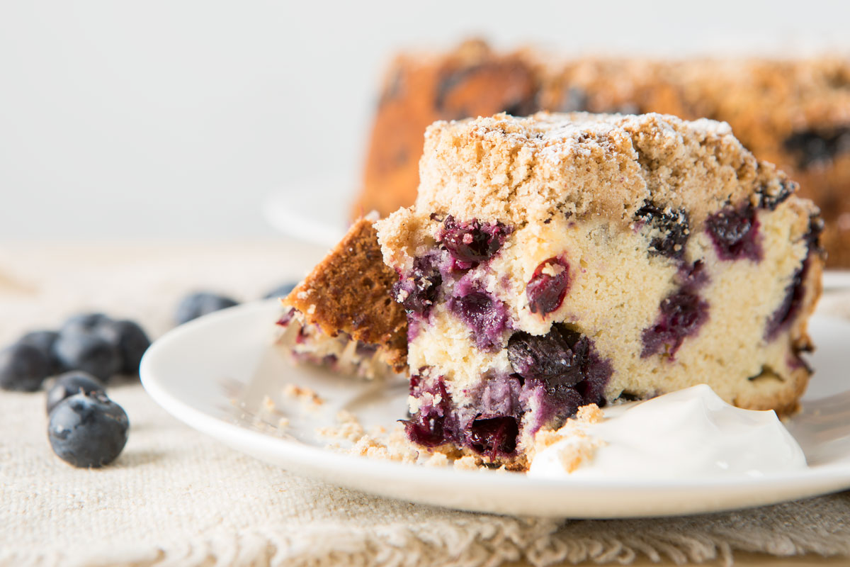 slice of blueberry buckle cake on a plate & slice of blueberry buckle cake on a plate - Nugget Markets Image